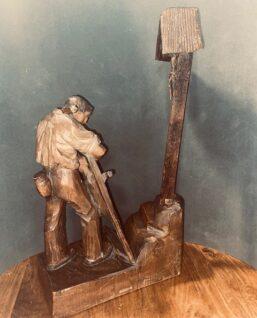 achterkant houtsnijwerk van boer bij kruis